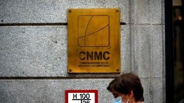 Una mujer pasa por el edificio de la CNMC, en Madrid
