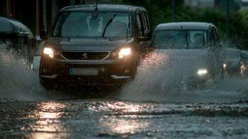 Vehículos circulan bajo una intensa lluvia en Orense.