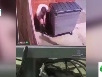 Un hombre haciendo sus necesidades tras un contenedor