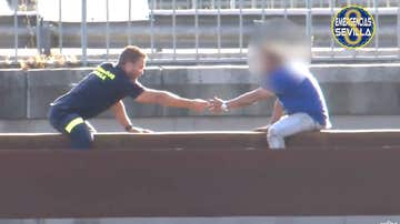 Un bombero rescata a un hombre encaramado a una viga