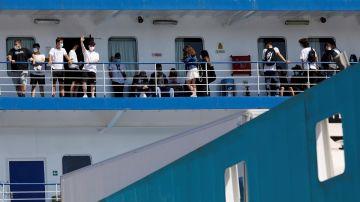 Varias personas saludan desde el ferry en el que viajan 118 estudiantes que habían sido confinados en un hotel de Mallorca tras el macrobrote.