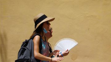 Varias personas se protegen del sol y el calor que se registra hoy en Córdoba