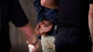Agentes de la Policía Nacional conducen a uno de los cuatro detenidos por el homicidio de Samuel Luiz al interior de los juzgados de A Coruña