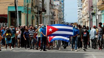 Un grupo de personas responden a manifestantes frente al capitolio de Cuba este domingo, en La Habana (Cuba).