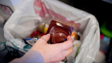Una persona echa un envase de yogurt a un cubo destinado a ello en su hogar