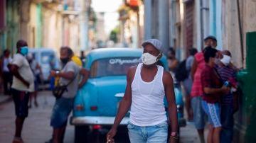 Un hombre camina por una calle con cubetas de huevos el martes 13 de julio del 2021, en La Habana