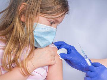 niña con mascarilla a la que le ponen una vacuna