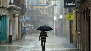 Un hombre camina bajo una intensa lluvia por el centro de la ciudad de Gandía