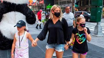 Personas con mascarilla caminan en Times Square en Nueva York