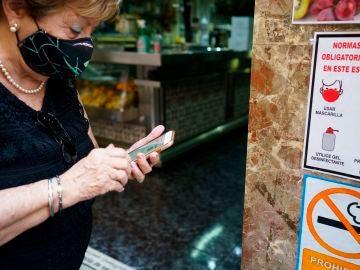 Una mujer busca en su móvil su certificado Covid momentos antes de acceder al interior de una cafetería de Santa Cruz de Tenerife