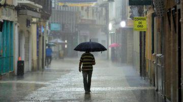 Un hombre camina bajo una intensa lluvia por el centro de la ciudad de Gandía, Valencia