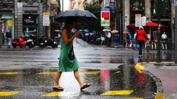 Una mujer se protege de la lluvia en el centro de Madrid