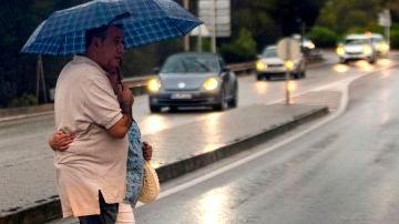 Una pareja pasea bajo un paraguas por las calles de Palma de Mallorca, este lunes.