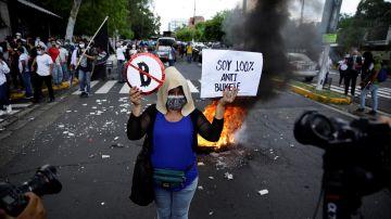 Una mujer participa en una marcha contra el bitcóin y el Gobierno de Nayib Bukele en San Salvador