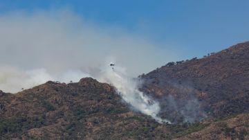 Un helicóptero realiza una descarga en una zona afectada por el incendio de Sierra Bermeja.