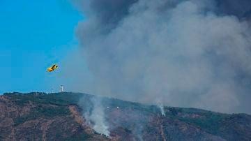Un hidroavión sobrevuela la zona quemada por el fuego del incendio de Sierra Bermeja