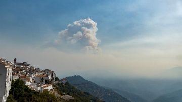 Vista del pueblo de Algatocín junto a una nube de humo que proviene del incendio