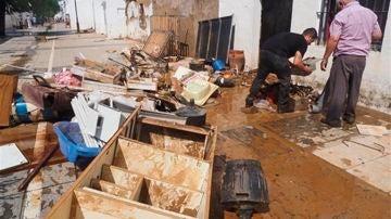 Vecinos de Lepe (Huelva) realizan labores de limpieza en su vivienda