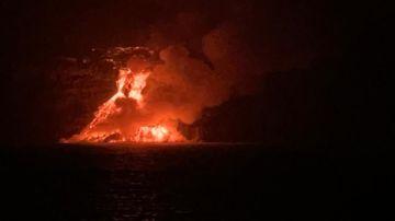 Imagen del cono que se está formando a los pies del acantilado con la lava en el mar.