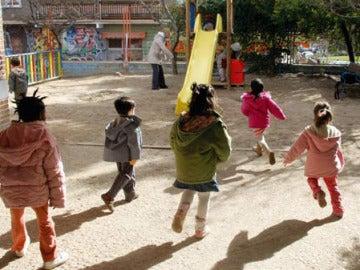 Varios niños salen a jugar a un parque infantil