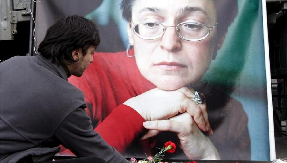 Un hombre deposita flores delante de un retrato de la periodista rusa Anna Politkóvskaya