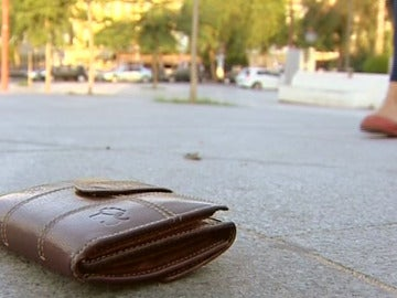 Una cartera perdida en el suelo de un parque