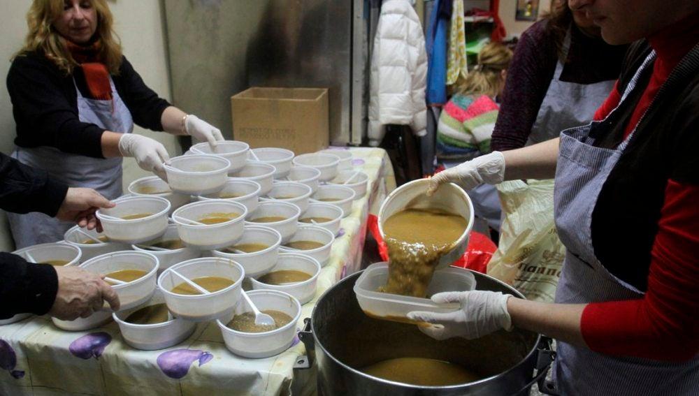 Varias mujeres preparan comida para los más necesitados