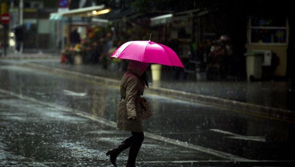 Una malagueña se protege de la lluvia con su paraguas
