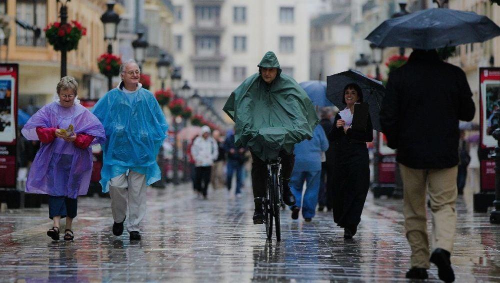 Los viandantes se resguardan de la lluvia