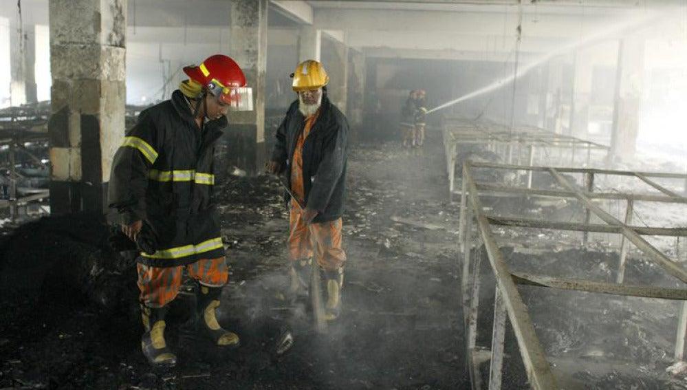 Trabajos de los bomberos en  el incendio de una fábrica textil en Bangladesh