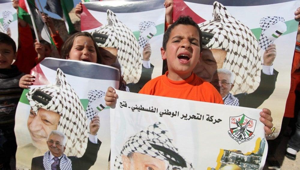 Niños palestinos con los retratos de Mahmoud Abbas y Yasser Arafat