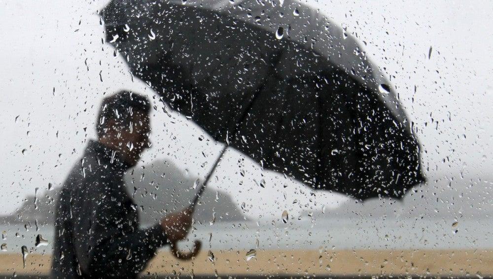 Un hombre pasea con lluvia junto a la bahía de La Concha de San Sebastián.