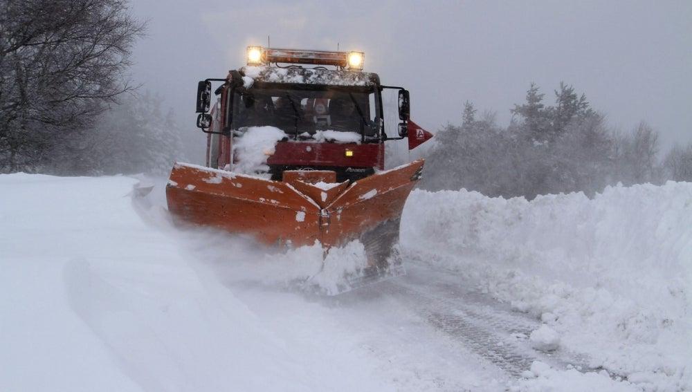 Un camión quitanieves retira la nieve acumulada en una carretera.