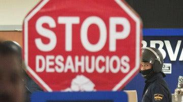"""Cartel de """"Stop Desahucios"""" delante de una sucursal del BBVA."""