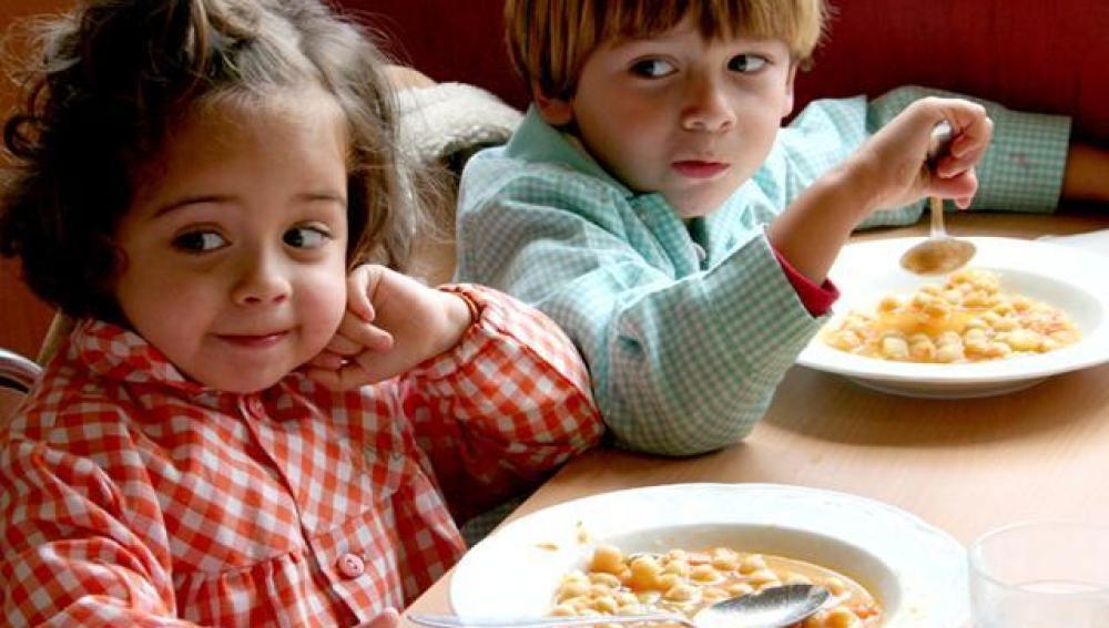 Dos niños comen garbanzos