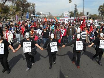 Miles de personas con fotografías de desaparecidos marchan en conmemoración del 40 aniversario del golpe de Pinochet