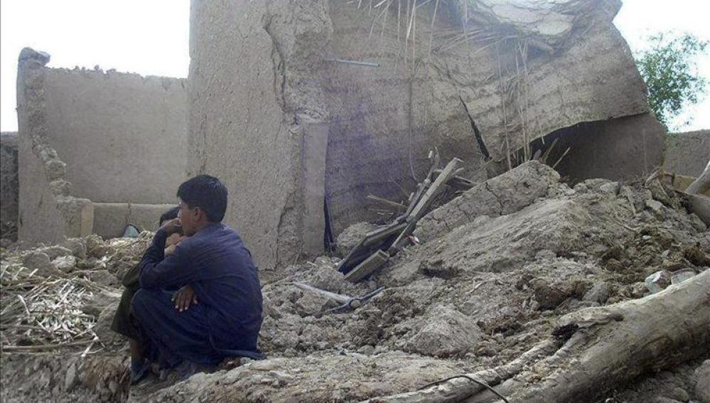 Varias personas permanecen junto a sus casas en ruinas tras el terremoto en Awaran
