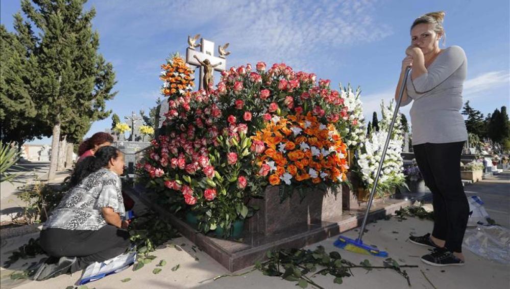 Varias mujeres colocan flores en la tumba de un familiar en el cementerio
