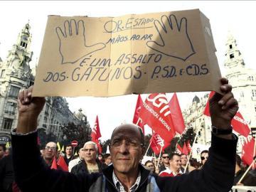 """Un hombre sostiene una pancarta en la que se lee """"Presupuestos generales del Estado, manos arriba"""