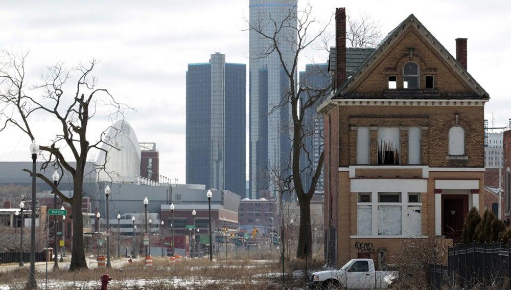 Casa abandonada con el edificio de General Motors de fondo, en Detroit, Michigan
