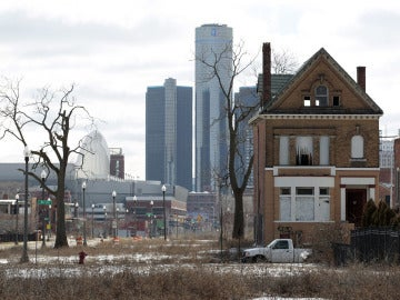 Casa abandonada con el edificio de General Motors de fondo, en Detroit, Michigan
