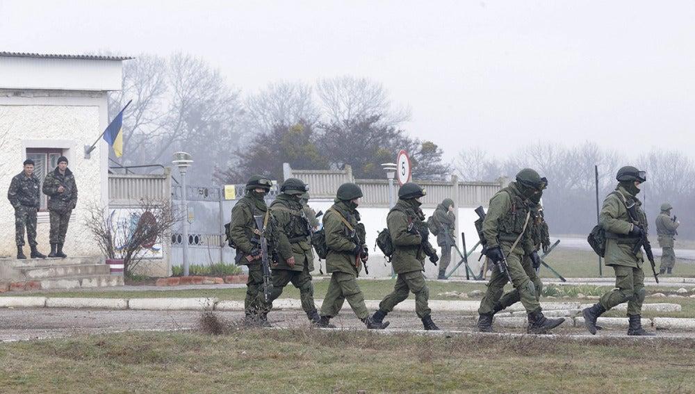Soldados ucranianos observan a un grupo de militares armados uniformados