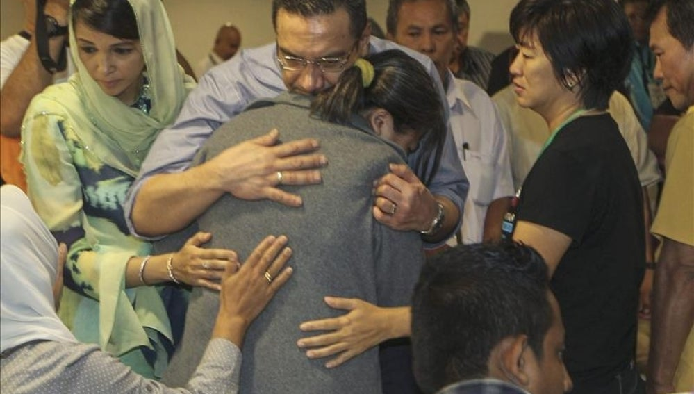 El ministro malasio de Defensa, Hishamuddin Hussin, consuela a un familiar de uno de los pasajeros