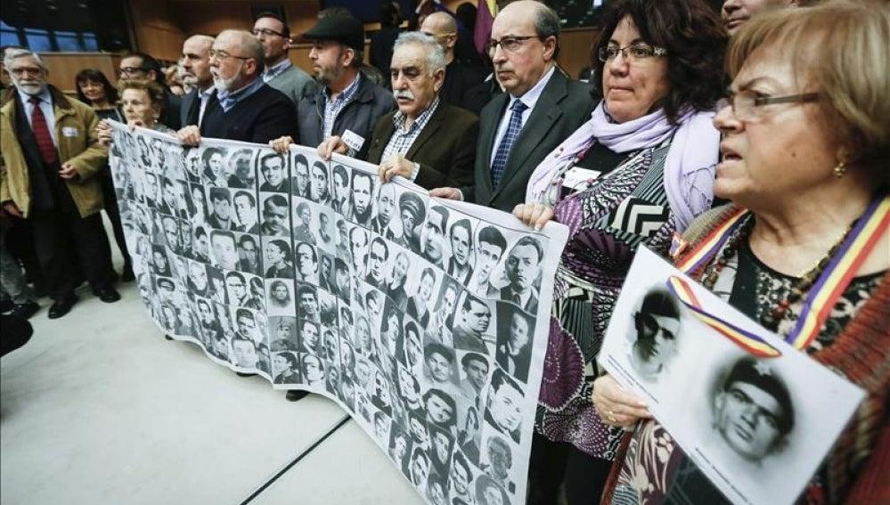 Familiares de las víctimas del franquismo muestran retratos de sus parientes