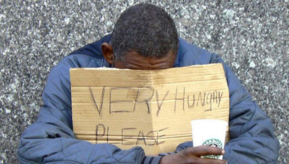 Un mendigo pide limosna en plena calle.