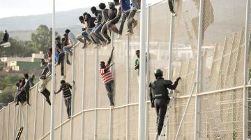 Inmigrantes encaramados en la valla de Melilla (Archivo)