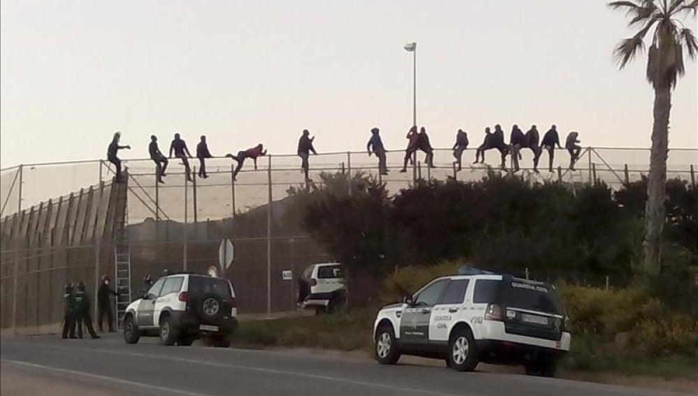Una quincena de inmigrantes permanecen encaramados en la valla