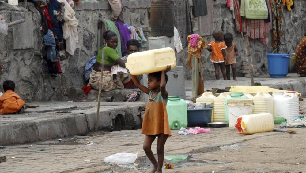 Una niña huérfana carga con un bidón para el agua en Bombai (India).
