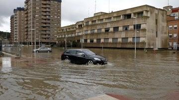 Un vehículo intenta circular en Miranda de Ebro, debordada tras la crecida del río Ebro.