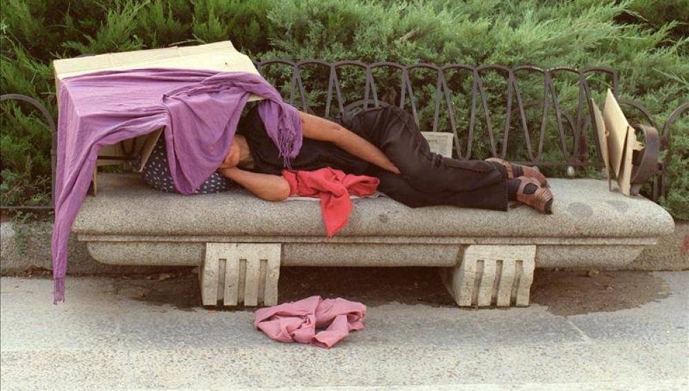 Una persona duerme en un improvisado refugio, imagen de archivo